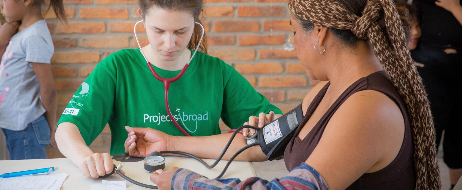 Medical volunteer measures the blood pressure of a local in Mexico